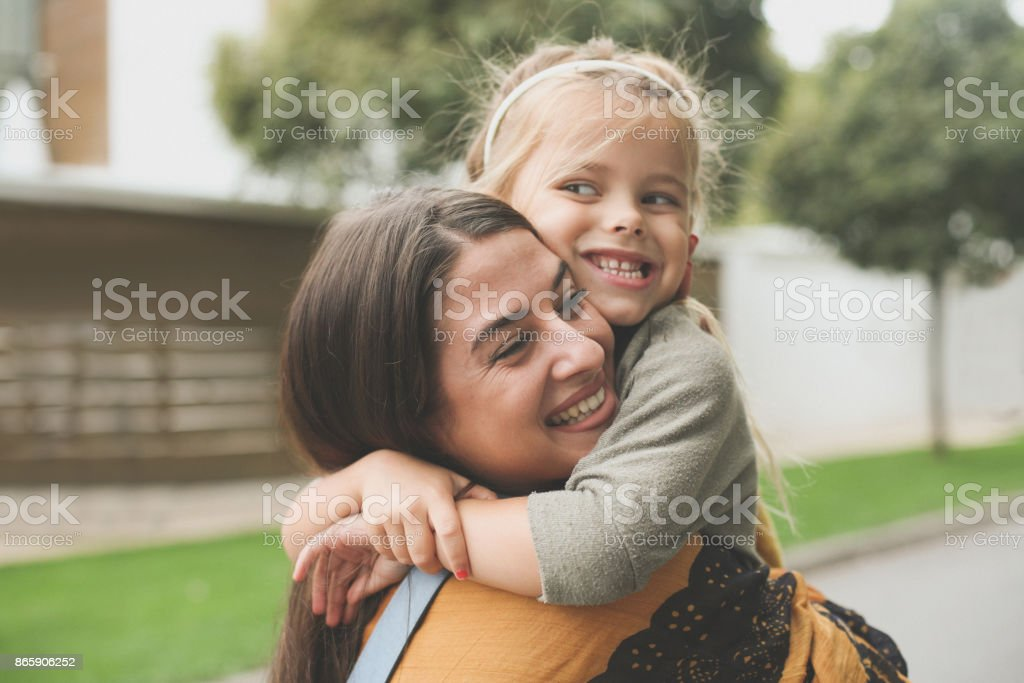 Kleines Mädchen in Moms Umarmung. – Foto