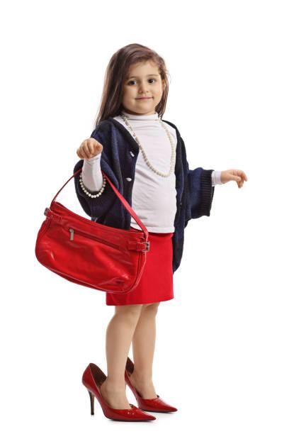 little girl in oversized high heels holding a handbag - kinderhandtaschen stock-fotos und bilder