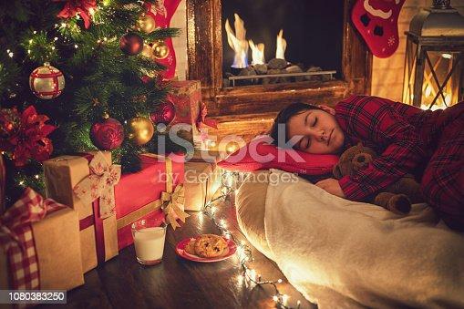 Beautiful little girl in pajama fell asleep near tree on Christmas Eve while waiting for Santa