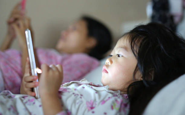 Little girl in pajamas with mother playing smartphone lying on a bed. stock photo