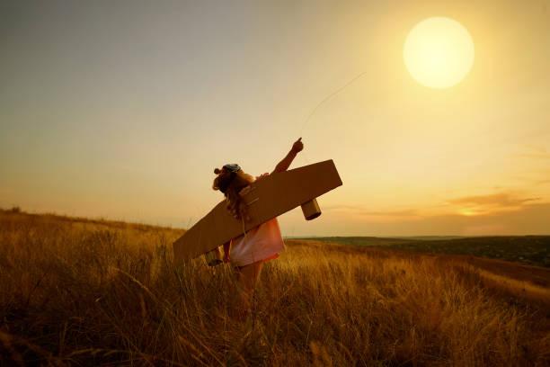 petite fille en costume de pilote dans domaine nature au coucher du soleil. - nuage 6 photos et images de collection