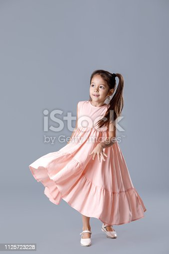 1128473714 istock photo little girl in pink dress posing on gray background. 1125723228