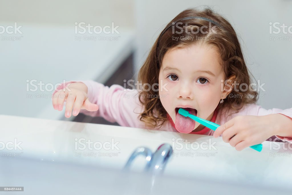 Little girl in pink pyjamas in bathroom brushing teeth stock photo