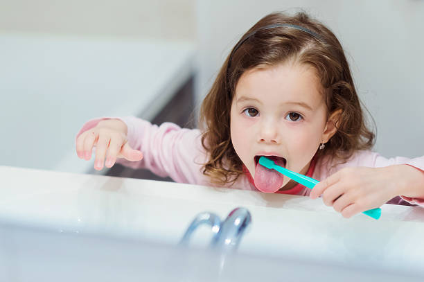 little girl in pink pyjamas in bathroom brushing teeth - mensentong stockfoto's en -beelden