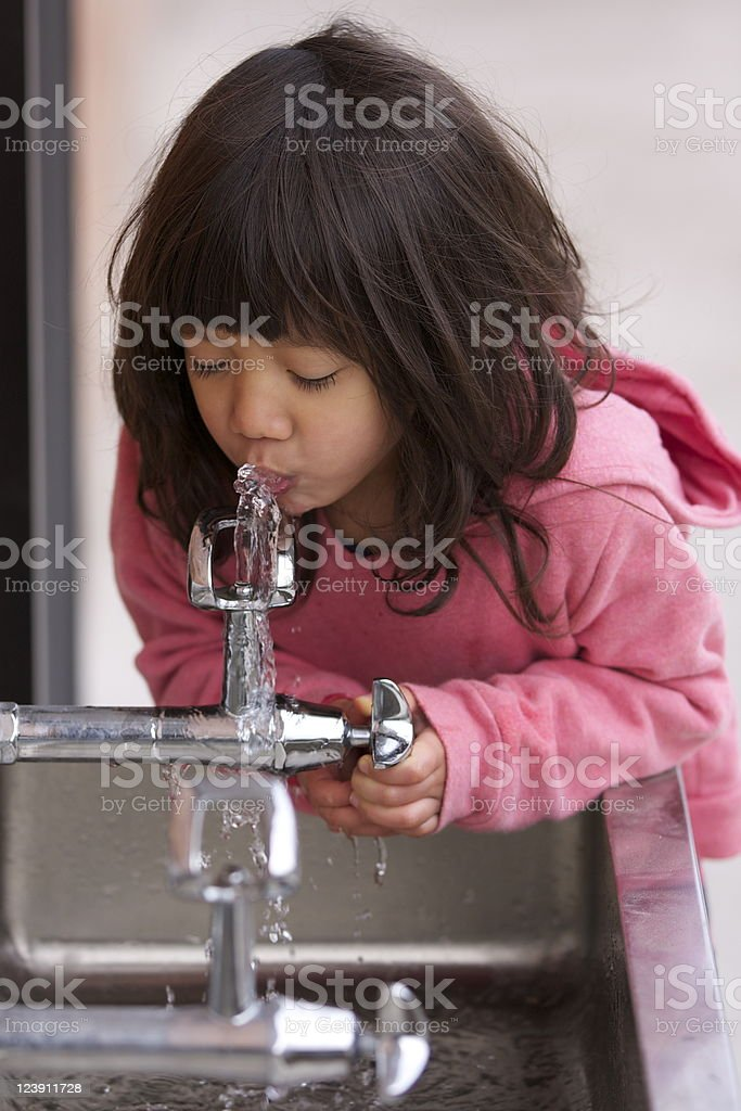 Little girl in pink sweater drinking from a water fountain stock photo