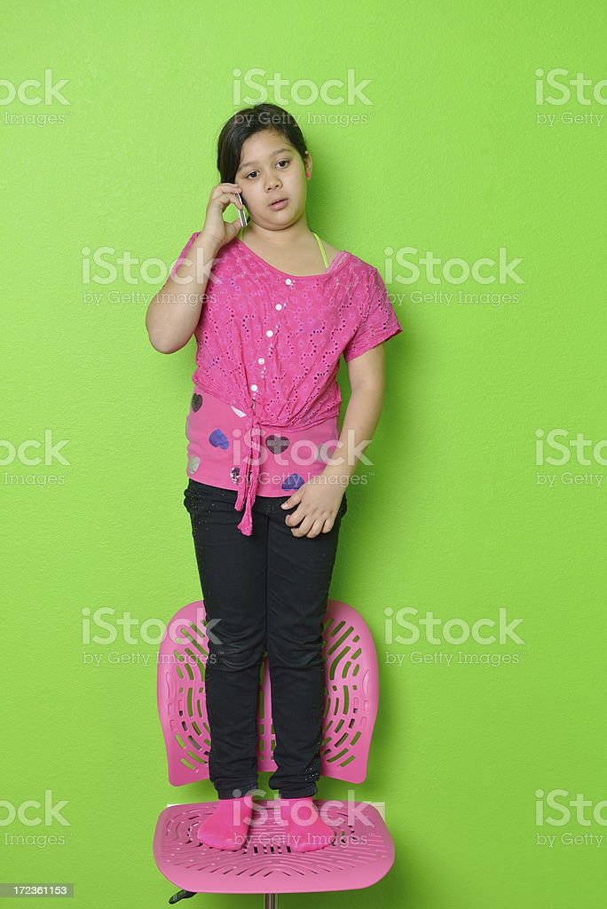 Little girl in pink talking on the phone royalty-free stock photo