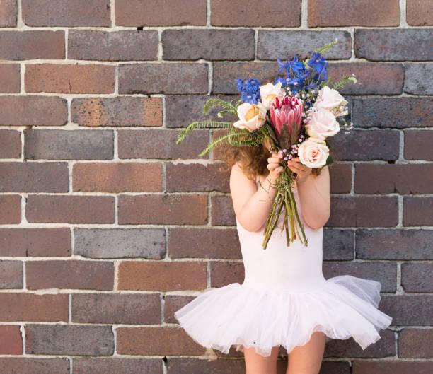 kleines mädchen im rosa tutu hält blumen außerhalb - protea strauß stock-fotos und bilder