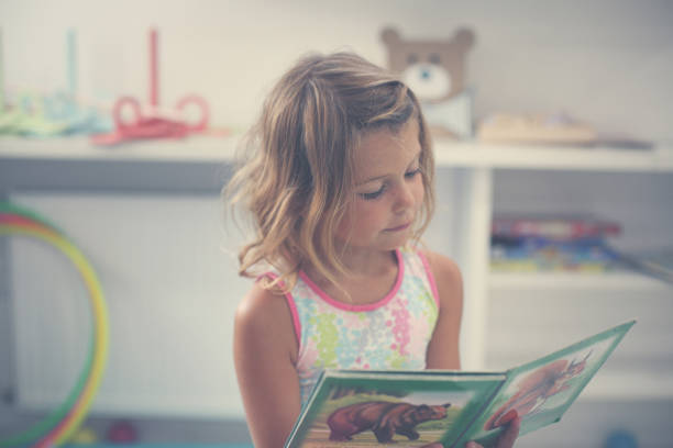 Little girl in playground. Little girl reading picture book. stock photo