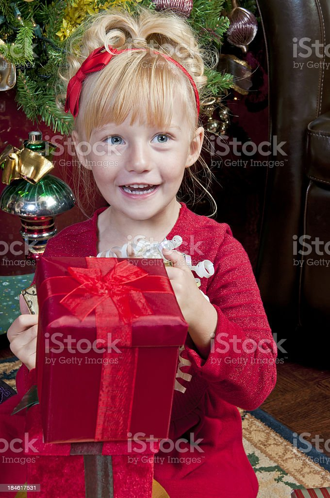 Little girl in red dress is opening Christmas presents