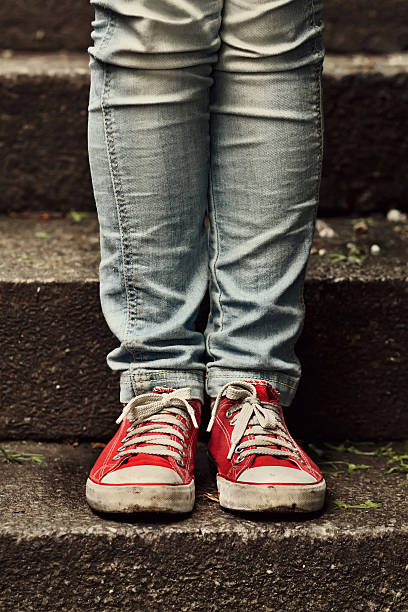 little girl in red sneakers standing on the stairs - dirty shoes stock photos and pictures