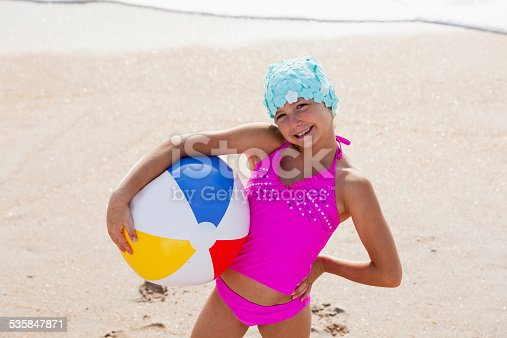 A cute little girl at the beach, holding an inflatable beach ball.  She is wearing a bright pink swimsuit and a retro swim cap, pretending to be a vintage bathing beauty.