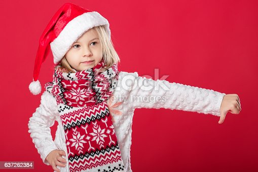 istock little girl in santa hat and scarf on red background 637262384