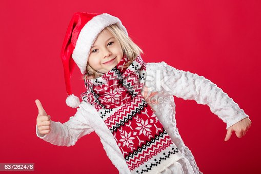 istock little girl in santa hat and scarf on red background 637262476