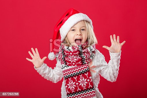 istock little girl in santa hat and scarf on red background 637263288