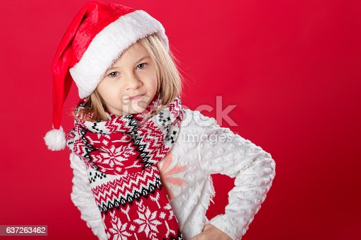 istock little girl in santa hat and scarf on red background 637263462