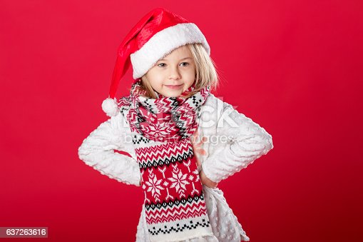 istock little girl in santa hat and scarf on red background 637263616
