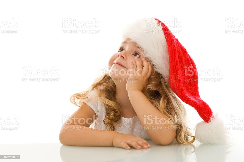 Little girl in Santa hat daydreaming of Christmas stock photo