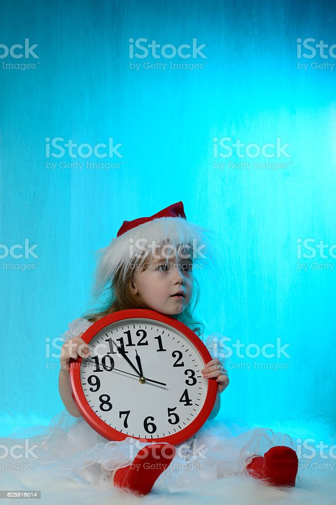 Little girl in santa hat with clock stock photo