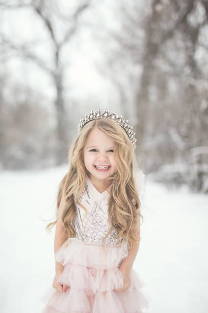 kleines mädchen im schnee - prinzessin kleid kind stock-fotos und bilder