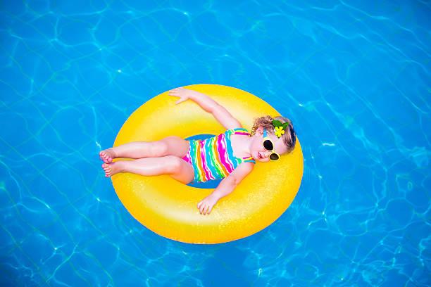 kleines mädchen im pool mit aufblasbaren ring - sonnenbrille kleinkind stock-fotos und bilder