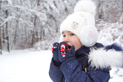 A little girl in the cold warms her hands in mittens-breathes warm air from her mouth on her hands. Winter, walk the baby in the open air, the snow. Warm clothing, knitted hat, fur pompom and hood