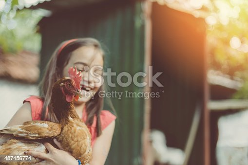 Laughing girl hoolding a hen
