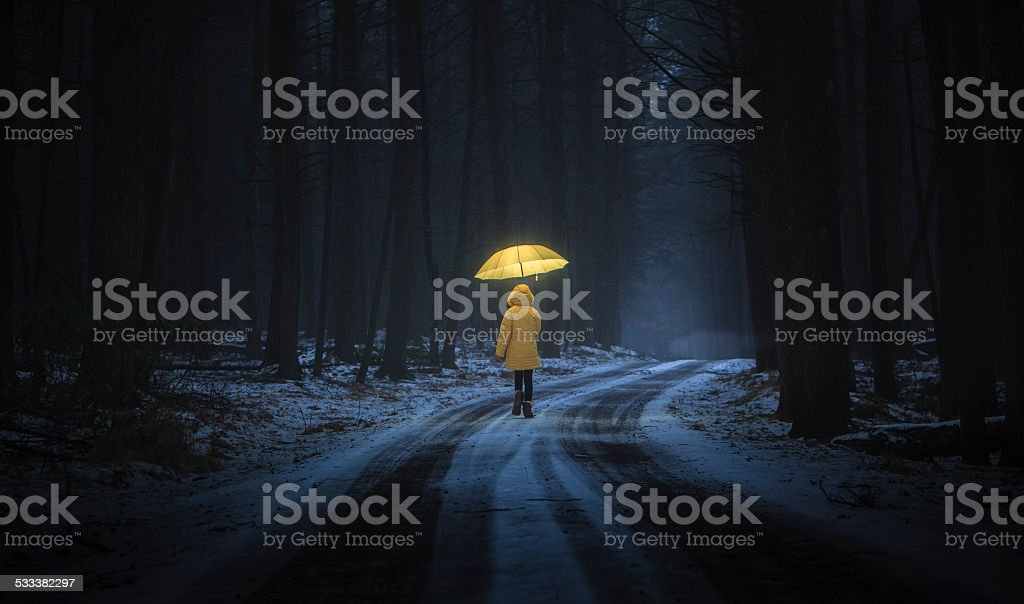 Little girl in the dark forest stock photo