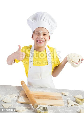 488109116istockphoto Little girl in the form of chef with an apron and cap smiles broadly and in one hand holds the dough, and in the other hand clenched her fist with a finger up blinks the dough with her hands 871616862
