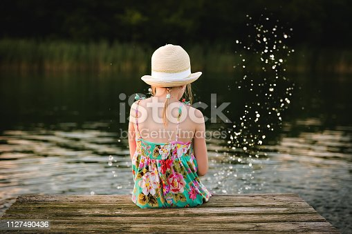 Little girl in the hat sitting on the jetty