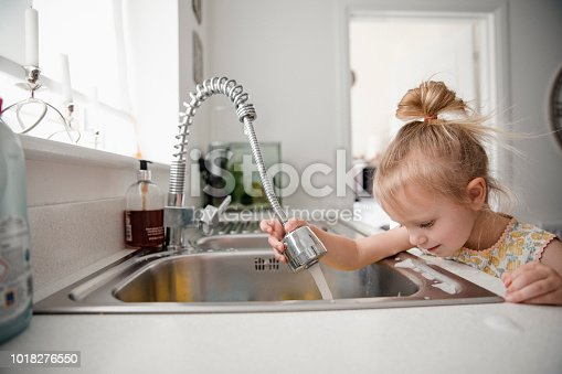 A side view of a little girl washing the dishes with water from the tap.