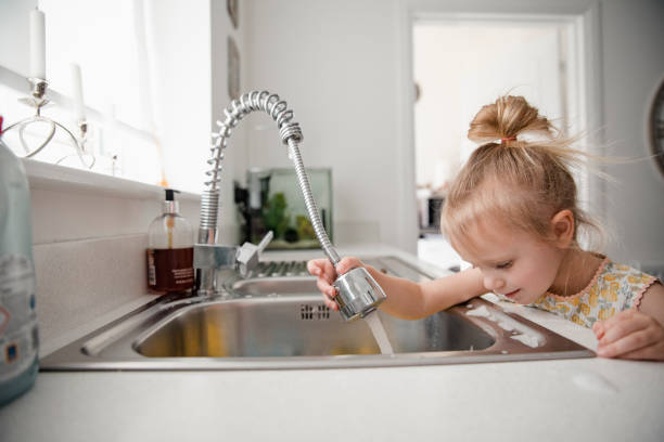 little girl in the kitchen - kitchen sink stock photos and pictures