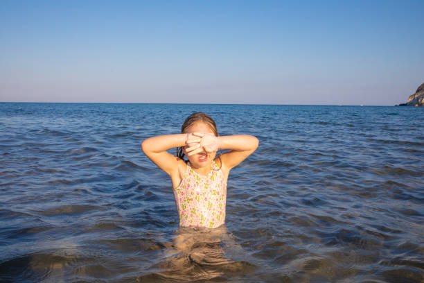 little girl in the water of sea covering her eyes with hands to protect herself from the sun little girl with swimsuit in the water of Mediterranean sea covering her eyes with hands to protect herself from the sun, in Cabo de Gata Natural Park (Almeria, Andalusia, Spain) dazzled stock pictures, royalty-free photos & images
