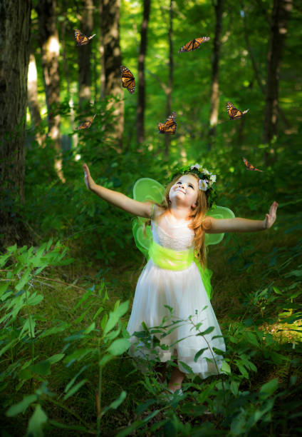 Little Girl in the Woods Releasing Butterflies stock photo