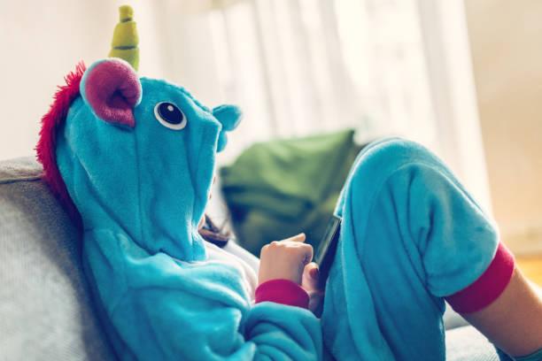 kleines mädchen mit einhorn kostüm mit mobile auf couch entspannen - jumpsuit blau stock-fotos und bilder