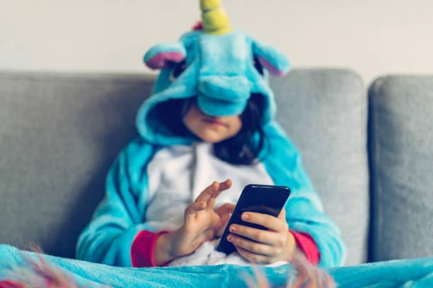 kleines mädchen mit einhorn kostüm, tippen sie auf mobile - jumpsuit blau stock-fotos und bilder