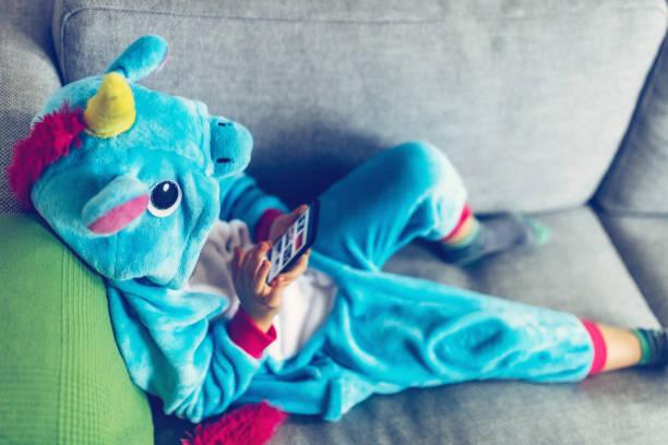 kleines mädchen mit einhorn kostüm auf dem handy ansehen - jumpsuit blau stock-fotos und bilder