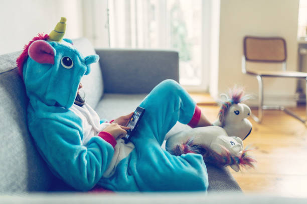 little girl in unicorn costume with mobile on couch stock photo