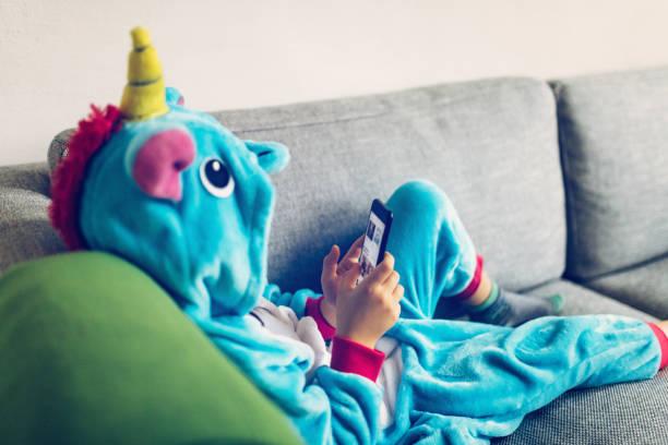 kleines mädchen mit einhorn kostüm mit mobile auf couch - jumpsuit blau stock-fotos und bilder