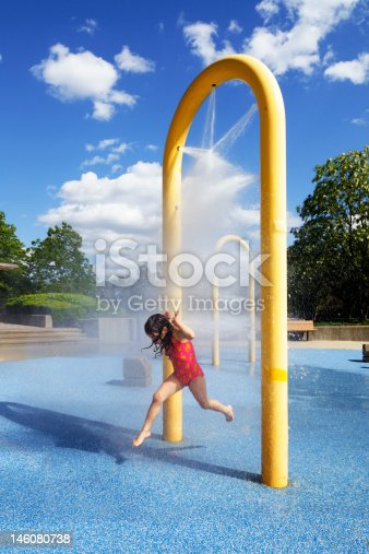Child running in water park during early summer. Little girl having fun.
