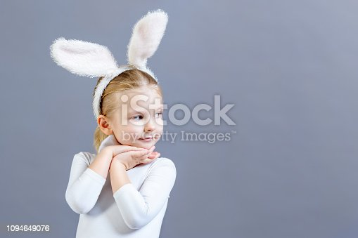 155096501 istock photo Little girl in white Easter bunny costume on a gray background. Beautiful baby looking towards copy space. Bright festive photo with space for text or advertising. 1094649076