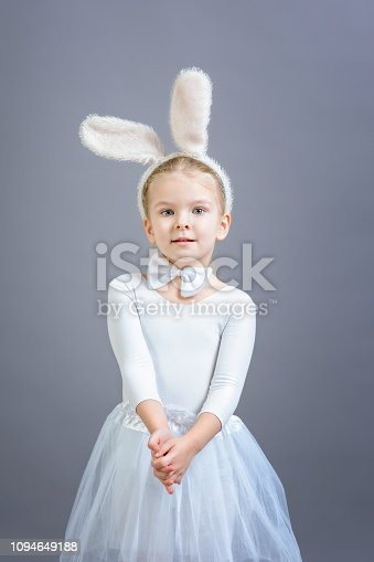 155096501 istock photo Little girl in white Easter bunny costume on a gray background. Beautiful portrait. Cute holiday symbol. 1094649188