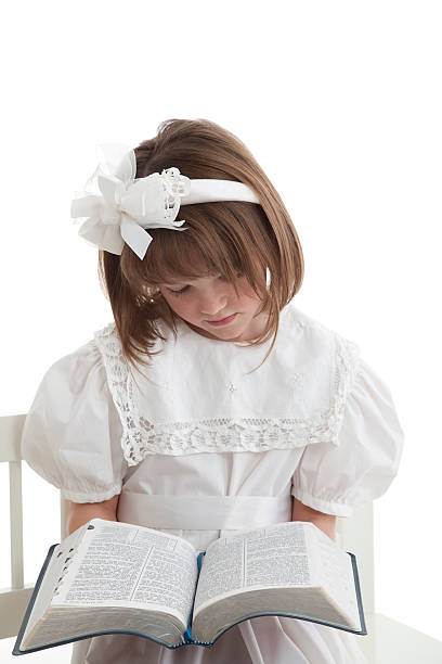Little Girl In White Reading Her Scriptures stock photo