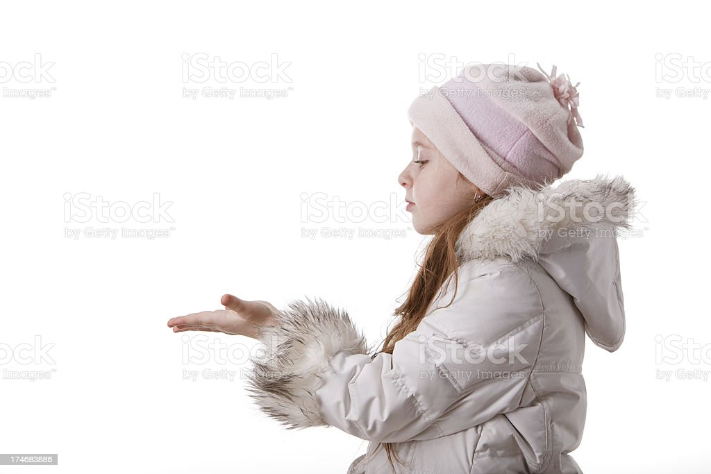 Little girl in white wintwr coat show something on palms royalty-free stock photo
