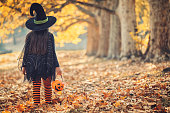 Little girl in witch costume having fun outdoors on Halloween trick or treat