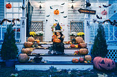 istock Little girl in witch costume sitting on the stairs in front of the house and holding Jack-o-Lantern Pumpkins on Halloween trick or treat 1254722161