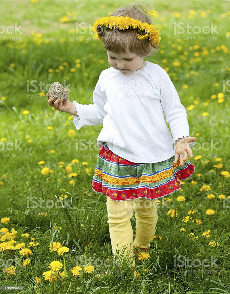 Little girl in yellow chaplet playing on dandelion meadow royalty-free stock photo