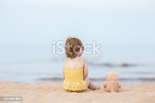 istock Little girl in yellow swimsuit and brown teddy bear sitting on beach sand and staring at sea water in warm sunny summer day. Back view. Looking far away. 1324697664