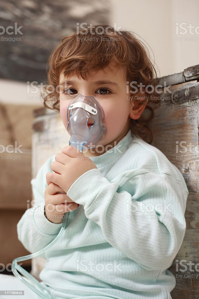 Little girl inhaling at home stock photo