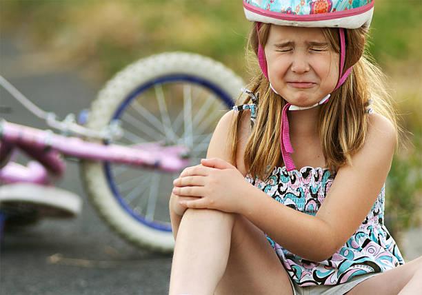 kleines mädchen auf fahrrad-unfall verletzt - kinderfahrrad stock-fotos und bilder