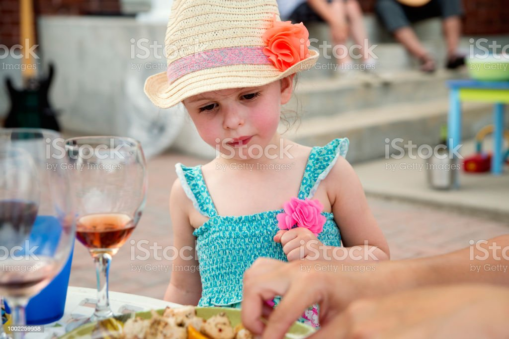 Little girl interested by mother's plate on family gathering. stock photo